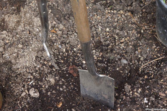 garden fork and garden spade in soil