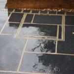 black limestone patio, manhole cover
