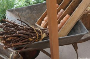 wheelbarrow, clay pots, bundle of sticks, garden sundries
