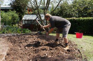 Nathan breaking up clods of clay, memory garden, plews garden design, plews garden landscaping, st christophers hospice, nathna waterfield