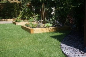 new turf lawn and raised vegetable beds, slate seating area, wooden raised beds around patio, family friendly garden