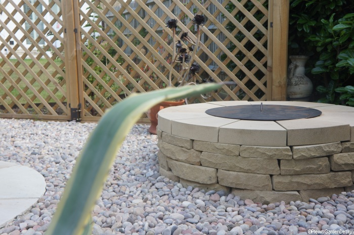 circular dry stone wall fire pit and aloe in garden entertaining area, diamond trellis fence, circular patio, decorative pebbles, garden project, kent